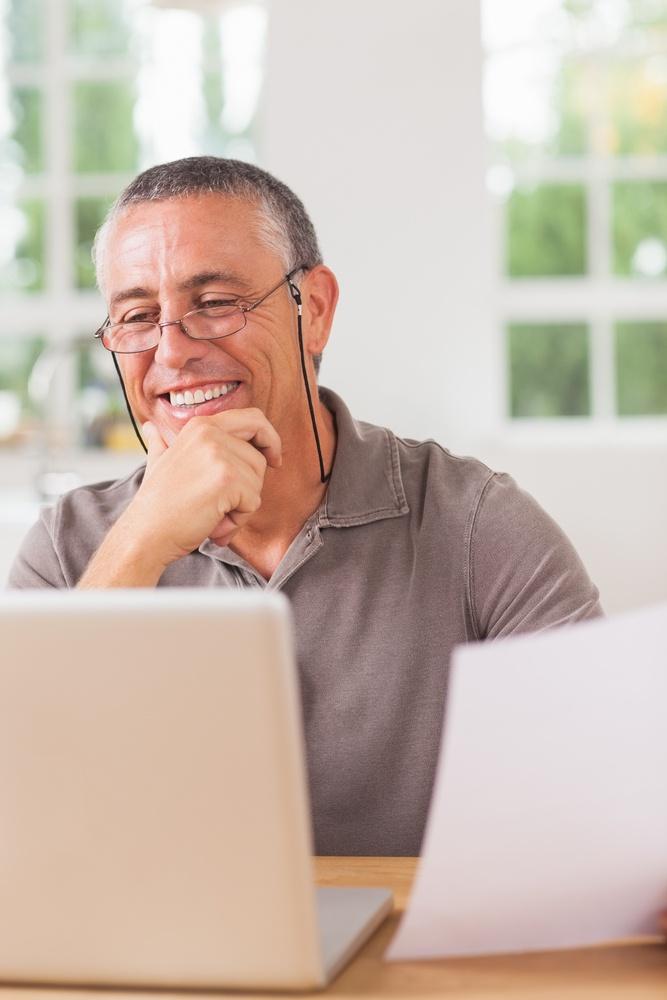 Happy man working at laptop in kitchen.jpeg