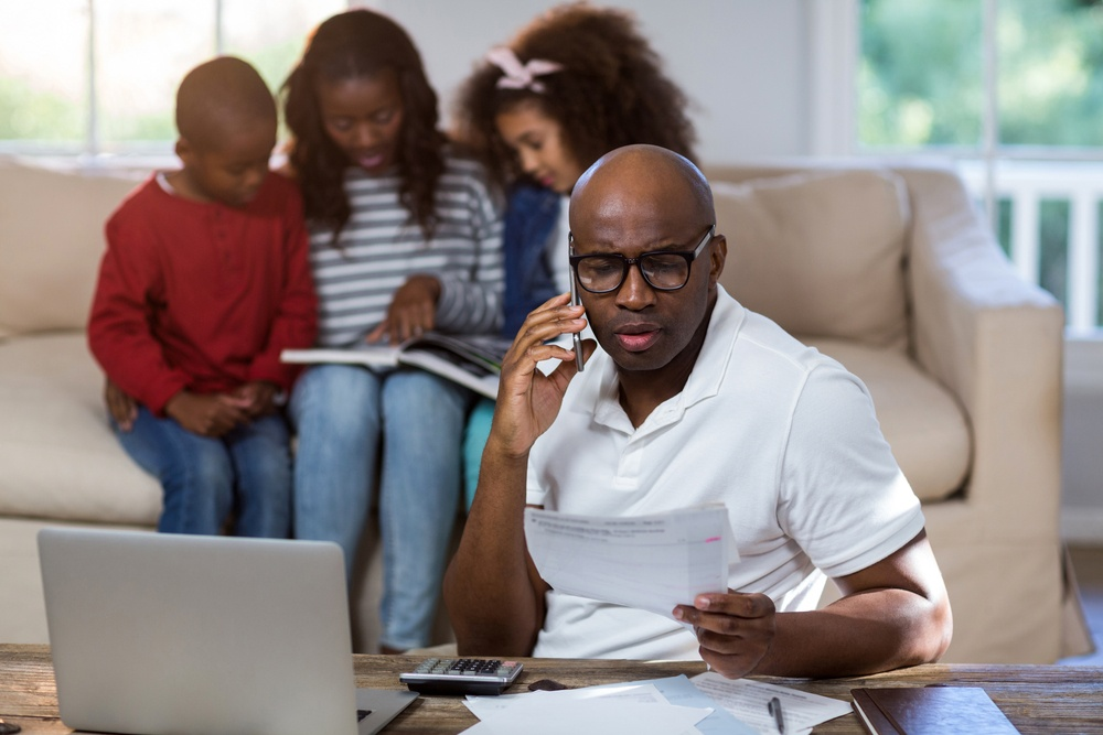 Man talking on mobile phone while checking installment loan status at home