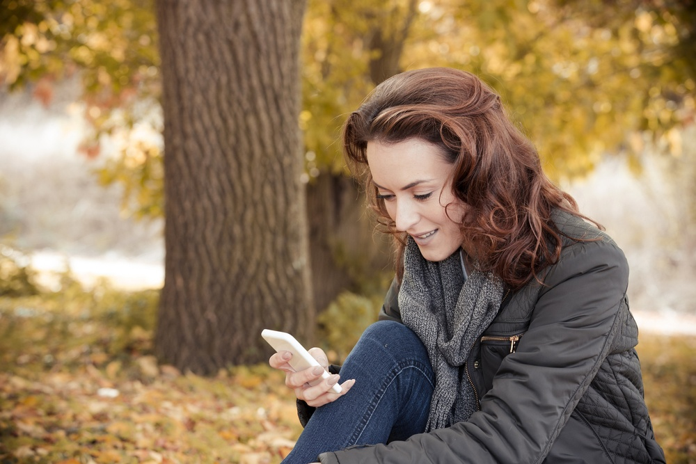 Young woman enjoying a autumn walk while texting with friends on her phone.jpeg